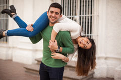 Carrying my girlfriend just for fun. Cute Hispanic young couple laughing and having some fun  hanging out in the city Royalty Free Stock Photography