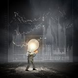 Carrying out an idea. Young businessman carrying light bulb on back Royalty Free Stock Photography