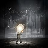 Carrying out an idea. Young businessman carrying light bulb on back Stock Photography