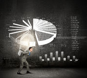 Carrying out an idea. Young businessman carrying light bulb on back Royalty Free Stock Images
