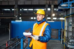 Carrying out Inventory at Modern Plant. Confident bearded technician wearing reflective vest and protective helmet standing at spacious production department of Stock Photography