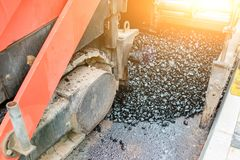 Carrying out repair works: asphalt roller stacking and pressing hot lay of asphalt. Machine repairing road.  Royalty Free Stock Image