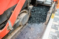 Carrying out repair works: asphalt roller stacking and pressing hot lay of asphalt. Machine repairing road.  Royalty Free Stock Photography