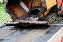 Carrying out repair works: asphalt roller stacking and pressing hot lay of asphalt. Machine repairing road.  Royalty Free Stock Photos