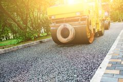 Carrying out repair works: asphalt roller stacking and pressing hot lay of asphalt. Machine repairing road.  Stock Photography