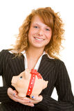 Carrying a piggy bank. Young redhaired woman in a business suit carrying a big piggy bank Stock Photography