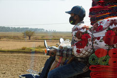 Carrying quilts and bedding on motorcycle Stock Images