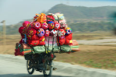 Carrying quilts on motorcycle. Carrying quilts and bedding on back of motorcycle, Skoun,  Cambodia Royalty Free Stock Photo
