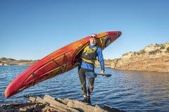 Carrying river kayak on lake shore Stock Photography