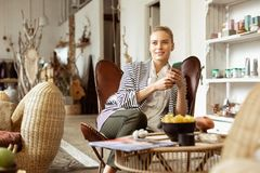 Beaming good-looking woman in elegant outfit lying in leather armchair. Carrying smartphone. Beaming good-looking woman in elegant outfit lying in leather stock images
