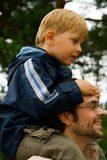 Carrying the Son. Smiling father carrying his little son on his shoulders Royalty Free Stock Photo