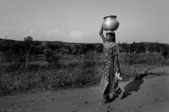 Carrying water. A woman is carrying water from distance to her village. She is lived in a village nearby jaduguda uranium mine. Due to radiation the water level Royalty Free Stock Images