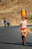 Carrying water. Young girl carrying bucket with water on her head to her mountain village on the central plateau in Madagascar Royalty Free Stock Photo