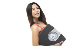 Carrying a weight scale. A beautiful Asian woman holding a sacle in her arm Royalty Free Stock Photo