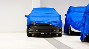 Cars. Covered by a blue tarpaulin dealer Stock Photography