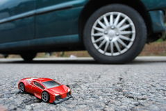 Cars. Children's sport car toy with real car in background Royalty Free Stock Photography