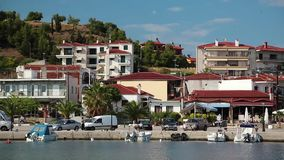 Cars and boats in harbour in Nea Skioni village in Greece stock video