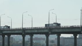 Cars on the bridge. Cars, trolleybuses and cyclist riding across the bridge on a cloudy day stock footage
