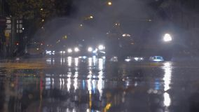 Cars with bright headlights in the city at rainy autumn night. PARIS, FRANCE - SEPTEMBER 29, 2017: Autumn drizzle in night city. View to the road with puddles stock footage
