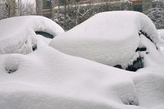 Cars buried in snow on moscow street after a great snow storm. In February 2018 Stock Photos