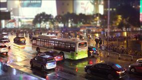 Cars and buses drive down the street with illuminated advertising and flashlights, people with umbrellas are walking