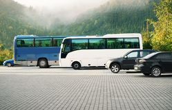 Cars and buses in a parking lot. On mountains background Royalty Free Stock Photo