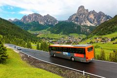 Cars & buses traveling on a scenic highway thru a green grassy valley royalty free stock photo
