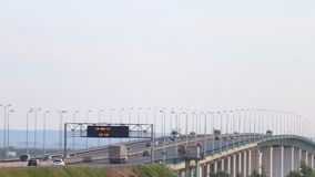 Cars, buses and trucks move on bridge. With time board, text translation - Kama river stock video