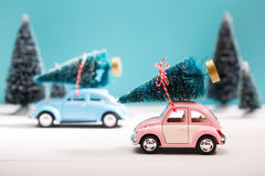 Cars carrying Christmas trees in miniature evergreen forest. Cars carrying Christmas trees in a snow covered miniature evergreen forest Stock Photo