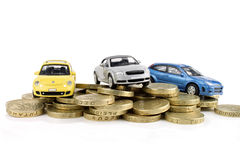 Cars On Cash. Three cars on a pile of gold coloured coins Royalty Free Stock Image