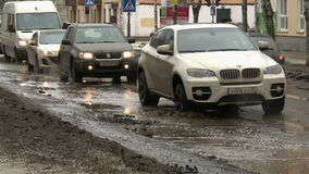 Cars in the city go around big holes. stock footage