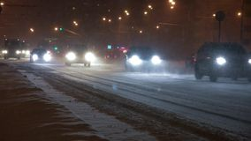 Cars on the city road in a snowstorm at night. stock video footage