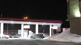 Cars come to petrol station and refuel at night in winter stock video