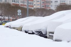 Cars completely covered with snow on parking. Cars completely covered with snow on parking in the city yard during snowfall Stock Photos