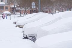 Cars completely covered with snow on parking. Cars completely covered with snow on parking in the city yard during snowfall Stock Image