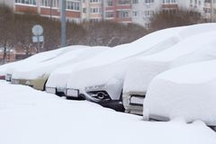 Cars completely covered with snow on parking. Cars completely covered with snow on parking in the city yard during snowfall Royalty Free Stock Photos