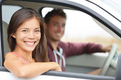 Cars - couple driving in new car smiling happy. Looking at camera. Young people on road trip drive in car. Beautiful interracial couple in their twenties, Asian Royalty Free Stock Photography