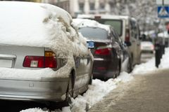 Cars covered in snow on a parking lot in city area after winter snowfall. Cars covered in snow on a parking lot in city area after winter snowfall Stock Photo
