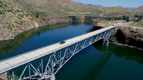 Cars cross a bridge from one side of a reservoir to the other stock footage