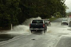 Cars crossing flooded road Royalty Free Stock Photo