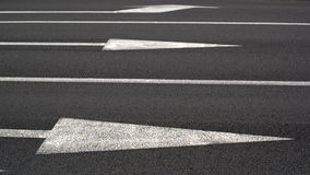Cars crossing smooth road. One-way traffic. Cars in motion. Focus on white lines and arrows as road marks and tires of cars. Royalty Free Stock Photos