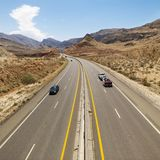 Cars on desert highway. Royalty Free Stock Images