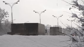 Cars drive on a winter city road behind a snowdrift. Part 1. stock footage