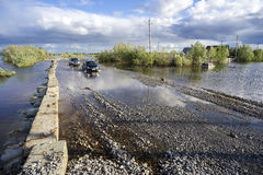 Cars drive on a flooded road. Royalty Free Stock Images