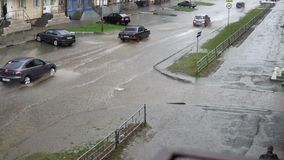 Cars drive on a flooded road in the rain, slow motion. A splash from cars as they pass through flood water after heavy rains. Flooded city road with big puddle stock video footage