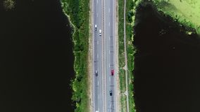 Cars drive on the highway located between the blue lake. 4k. Aerial drone footage. Cars drive on the highway located between the blue lake. The sky is reflected stock video