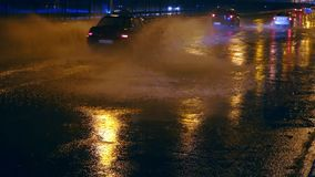 Cars drive into large puddles on the night road in the city, spray puddles scatter from under the wheels of the car. Light headlights reflected in puddles on stock video footage