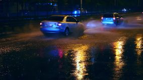 Cars drive into large puddles on the night road in the city, spray puddles scatter from under the wheels of the car. Light headlights reflected in puddles on stock footage