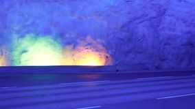 Cars drive in the Laerdal tunnel with colorful lighting stock video footage