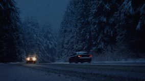 Cars Drive Through Snowstorm In The Evening. Moving shot of cars driving through snowy forest in the evening stock footage